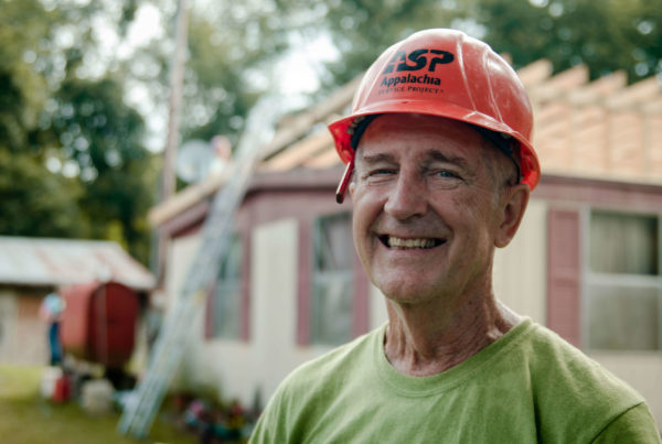 older male volunteer smiles while wearing orange ASP hardhat